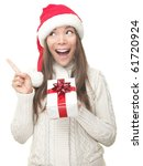 Christmas woman showing copy space pointing up to the side being excited and surprised. Isolated on white background. Young smiling woman in Santa hat showing copyspace. Asian / Caucasian female model - stock photo