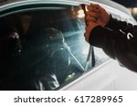 Male carjacker trying to open car door with ruler - stock photo
