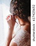 elegant brunette bride putting... | Shutterstock . vector #617425652