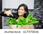 Small photo of Closeup portrait, young woman pointing to bag full of green groceries, healthy nutritious balanced diet, isolated indoors home background. Locally sourced food