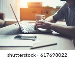 man using laptop at his... | Shutterstock . vector #617698022