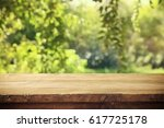empty rustic table in front of... | Shutterstock . vector #617725178