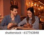 loving millenial couple sitting ... | Shutterstock . vector #617763848