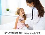 doctor examining a little girl... | Shutterstock . vector #617822795