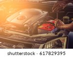 Stock photo car service fitting a car battery with wrench soft focus picture 617829395