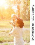 a young mother in a park... | Shutterstock . vector #617838842
