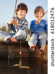 Stock photo happy boys go fishing on the river with pet two children and kitten of the fisherman with a 618012476