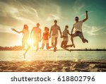 friends jumping on the beach... | Shutterstock . vector #618802796