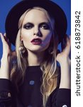 Small photo of Portrait of woman in black hat and black top on blue background