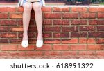 young woman sitting on brick... | Shutterstock . vector #618991322