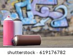 Small photo of A still-life of several aerosol paint spray cans lies on a roofing covering on the background of a brick wall, on which is painted a bright and colorful graffiti drawing. Items related to street art