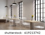 Stock photo side view of a cafe with square wooden tables with flowers on them white chairs and tall windows 619213742