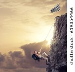 Small photo of Businessman climb a mountain to get the flag. Achievement business goal and difficult career concept