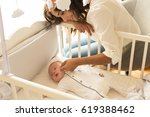 mother putting baby to sleep at ... | Shutterstock . vector #619388462