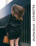Small photo of spring fashion outfit. woman wearing a black bomber jacket and a black dress. fashion blogger posing on the street. accessorized with a brown handbag. wind in hair. healthy hair in motion.