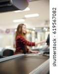 Small photo of Blurred picture of cashier lady on workspace in supermarket shop. Focus on desk.