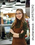 Small photo of Image of happy cashier woman on workspace in supermarket shop. Looking at camera.