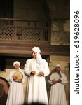 Small photo of CAIRO, EGYPT - CIRCA APRIL 2017: An old and fun Egyptian dervish dressed in white performs at a traditional tanoura concert accompanied by young dervishes.