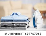 electric iron and pile of... | Shutterstock . vector #619767068