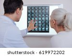 Stock photo pleasant male doctor showing his patient an x ray photo 619972202