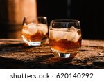 a glass of whiskey with ice on... | Shutterstock . vector #620140292