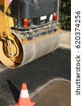 Small photo of detail of an heavy road roller on the road and a traffic cone