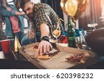 man eating stale pizza in messy ... | Shutterstock . vector #620398232