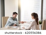 Small photo of Young male and female partners handshaking over the office table, showing mutual respect, greeting and starting negotiations, closing a deal or making an agreement sitting by the window