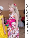 Small photo of A little girl of preschool age in a beautiful dress tells poems on a children's performance in a kindergarten