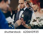 wedding couple putting on... | Shutterstock . vector #620643935