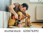 Stock photo man doing renovation work at home together with his small yellow dog 620676392