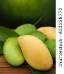 Small photo of Green and Yellow mangoes on wooden table, are generally sweet, although the taste and texture of the flesh varies across cultivars.