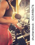 Small photo of Female fitness trainer in fitness club taking weights, concept