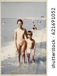Small photo of USSR, ABKHAZIA, LESELIDZE - CIRCA 1980: Vintage photo of little sister with little brother on Black sea beach in Abkhazia, USSR