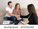 Small photo of Cheerful happy young couple purchasing apartment. Guy shaking hands with real estate agent, male property buyer and female realtor handshaking, investment advisor congratulating clients with deal