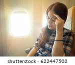 Small photo of portrait of brunette hair woman headache facial expression on a chair. fear of flying student in plane with pain airsickness with vintage retro film color.