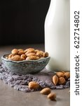 Small photo of Dairy alternative milk. Almond milk in a glass bottle and fresh nuts over a gray background, selective focus. Clean eating, dairy-free, vegan, vegetarian, allergy-friendly, healthy food concept.