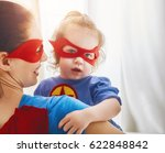 Small photo of Mother and her child playing together. Girl and mom in Superhero costume. Mum and kid having fun, smiling and hugging. Family holiday and togetherness.