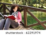 Young beautiful girl student sitting on wooden bridge over the river  in nature and reading a book - stock photo