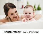 loving mother bathing her cute... | Shutterstock . vector #623140352