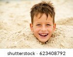 Small photo of little boy buried in the sand on beach