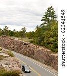 Car on a road through a rock cut - stock photo