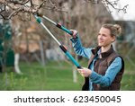 Girl gardener working in the spring garden and trimming tree  - stock photo