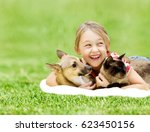 Stock photo little girl with a dog and a cat on a green grass 623450156