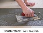 tile setter laying down thinset ...   Shutterstock . vector #623469356