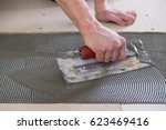 tile setter laying down thinset ... | Shutterstock . vector #623469416