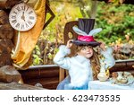 Stock photo an little beautiful girl in the scenery holding cylinder hat with ears like a rabbit over head at 623473535