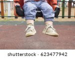 child sitting on swing in park | Shutterstock . vector #623477942
