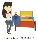 asian woman putting jacket into ... | Shutterstock .eps vector #623503076