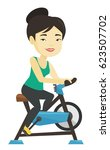asian woman riding stationary...   Shutterstock .eps vector #623507702